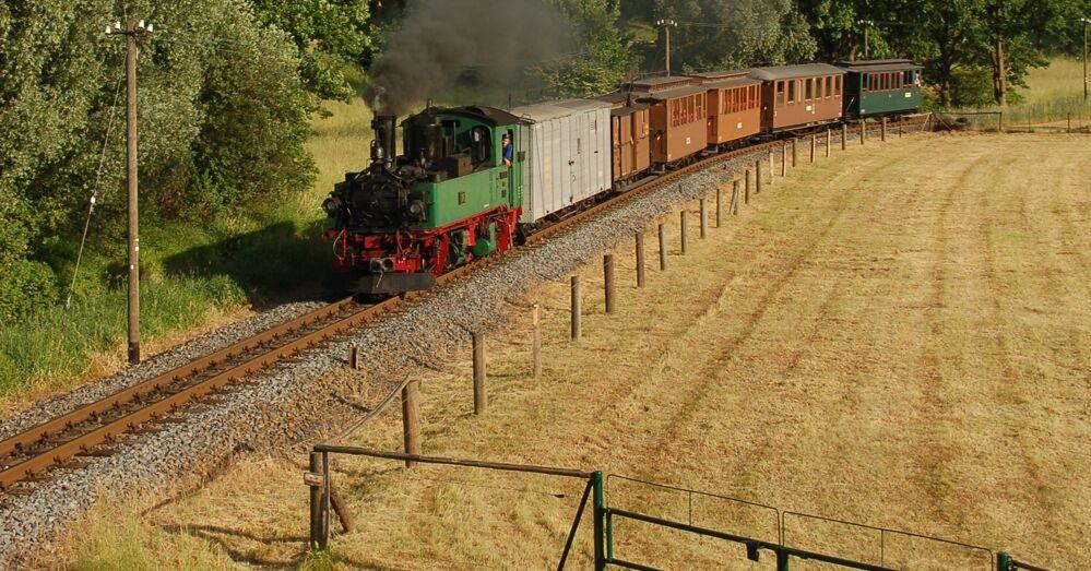 Grüne Dampflok mit Personenwagen mit brauner Holzbelankung und grauem Gepäckwagen